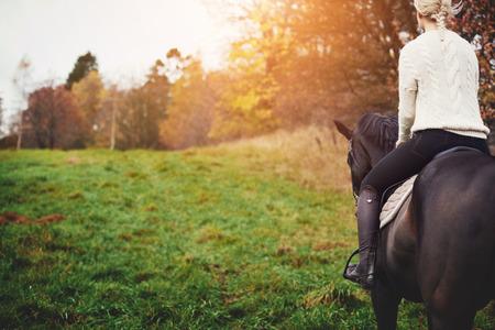 Junge Frau im Reitgang, der in einem Sattel auf einem Kastanienpferd sitzt, während heraus für Fahrt in die Landschaft im Herbst