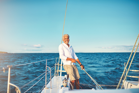 Smiling mature man standing on his boat deck while out for a sail along the coast on a sunny day 写真素材