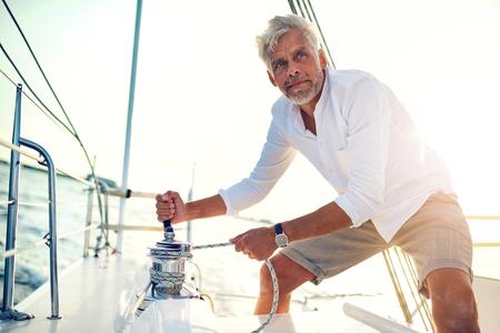 晴れた午後に帆のために外にウィンチを使用して彼のボートのデッキに立っている成熟した男性