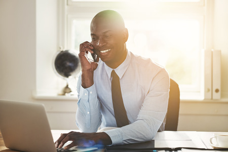 Smiling young African businessman talking to a client on his cellphone while sitting at his desk in an office