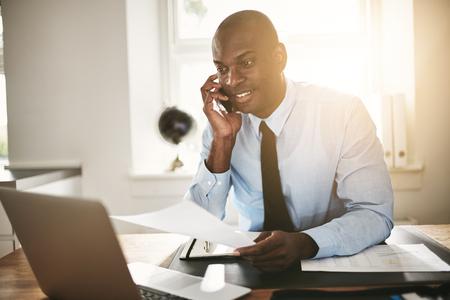 사무실에서 그의 책상에 앉아있는 동안 그의 핸드폰에 클라이언트 얘기하는 젊은 아프리카 비즈니스 전문가 미소