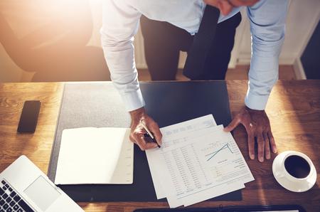 Fälliger Finanzberater, der ein Hemd und eine Bindung sich lehnt über seinem Schreibtisch in Bürounterzeichnenden Kontopapieren trägt Standard-Bild