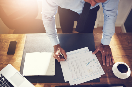 Mature financial consultant wearing a shirt and tie leaning over his desk in an office signing account papers