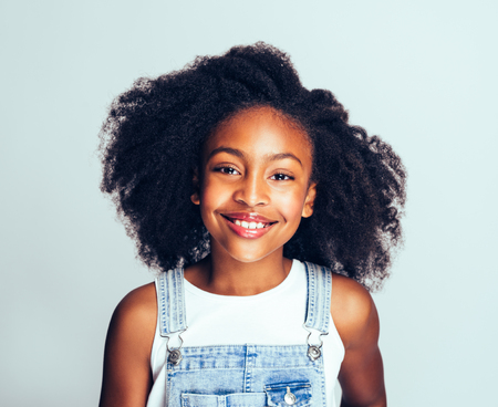 Smiling young African girl with long curly hair wearing dungarees standing happily against a gray background