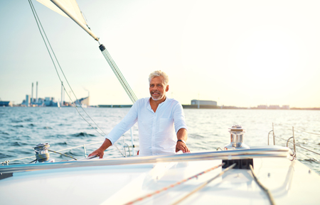Smiling mature man standing on the deck of a boat sailing along the coast on a sunny day 写真素材