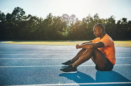 Geconcentreerde jonge Afrikaanse mannelijke atleet in sportkleding die alleen op een renbaan zitten die geestelijk op een race voorbereidingen treffen Stockfoto