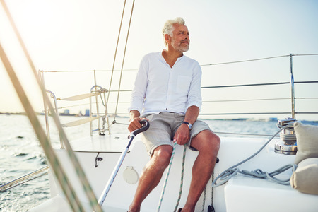 Mature man steering the rudder of his boat while out for a sail along the coast on a sunny day 写真素材