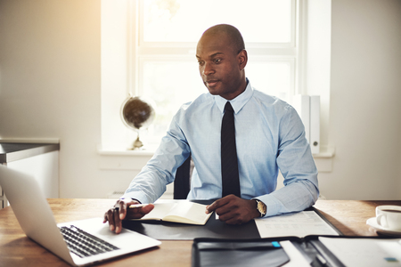 Focused young African businessman wearing a shirt and tie sitting at his desk in an office working online with a laptop Imagens