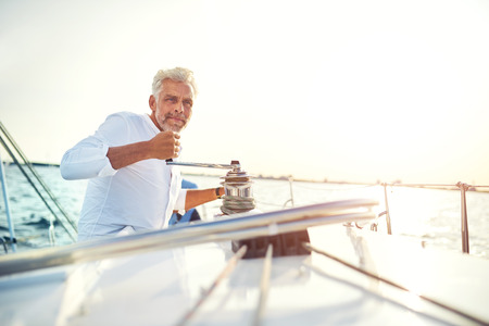 Mature man standing on the deck of a boat winding a winch while out for a sail on a sunny afternoon Imagens