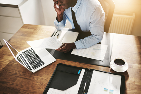 Young African businessman talking to a client on his cellphone while sitting at his desk in an office