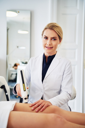 Smiling female technician performing a laser hair removal procedure on the legs of a young woman lying on a table in a beauty clinic Stock Photo