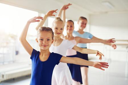 若い陽気な女の子バレエを実行して、クラスのカメラを見て笑っています。