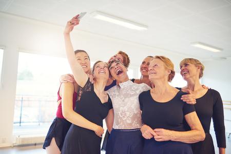 팔을 함께 서서 댄스 스튜디오에서 셀카를 취하면서 얼굴을 만드는 여성 그룹 웃음
