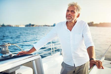 晴れた日に沿岸航行船の甲板に立っている中年の男性
