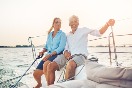 Smiling mature couple sitting on the deck of their boat while enjoying a day together sailing on a sunny afternoon Stock Photo