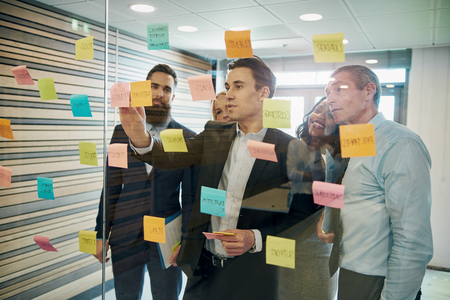 Group of business people brainstorming with sticky notes on glass window Stockfoto