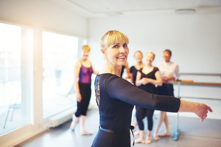 Active senior woman doing ballet in a dance studio with a group of friends in the background Stock Photo