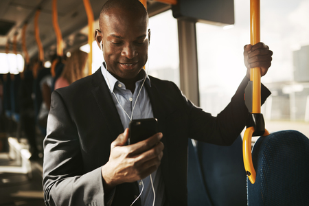 Smiling young African businessman wearing a suit standing on a bus during his morning commute listening to music on a smartphone and earphones