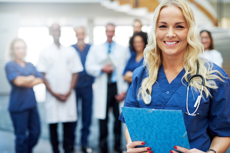 Female medical professional standing in a clinic and looking at camera. Team of doctors
