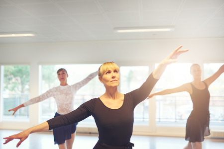 Group of adult women exercising and performing ballet dance together in the class.