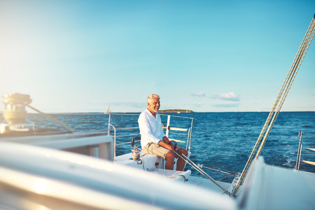 Smiling mature man sitting on the deck of his boat while sailing along the coast on a sunny day