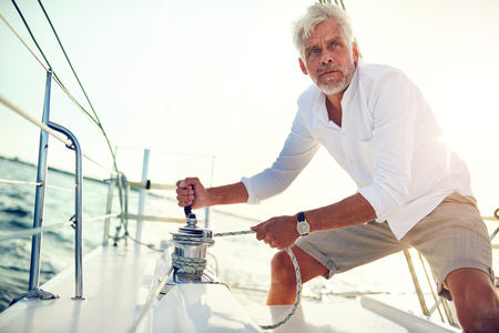 Mature man standing on the deck of a boat winding a winch while out for a sail on a sunny afternoon Stock Photo