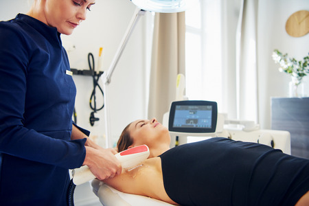 Young female beautician performing a laser hair removal procedure on the underarm of a woman lying on a table in a beauty clinic Stock Photo