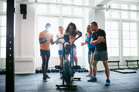 Group of smiling people cheering on their friend riding a stationary bike while working out together in a gym