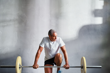 Senior man in sportswear kneeling in a gym preparing to lifting weights during a workout
