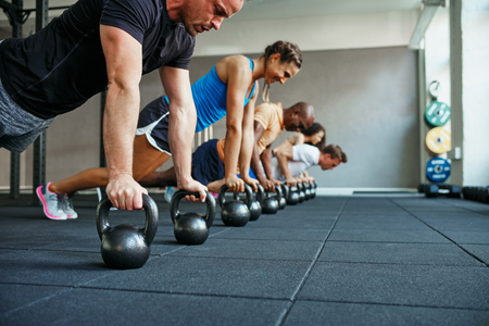 Group of fit people working out together on the floor with weights during a health club class Foto de archivo