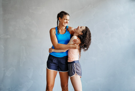 Two young girlfriends in sportswear standing arm in arm together in a gym laughing