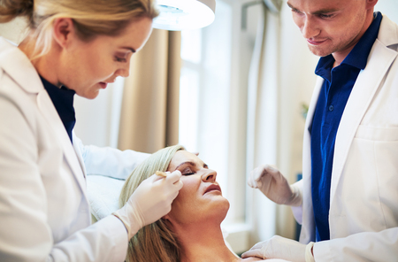 Two doctors planning a cosmetic facial surgery procedure on a mature woman lying with her eyes closed on a table in a clinic