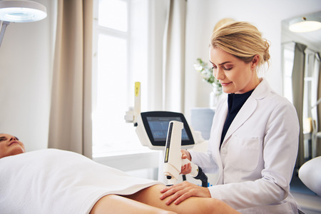 Female technician performing a laser hair removal procedure on the legs of a young woman lying on a table in a beauty clinic