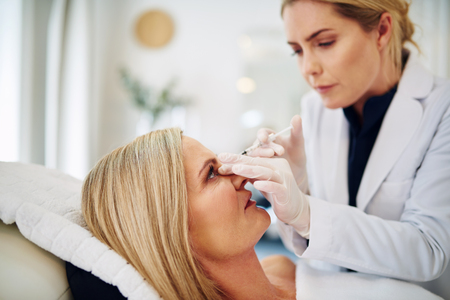 aging face: Female doctor performing a botox injection to the forehead of a mature woman lying on a table in a beauty clinic