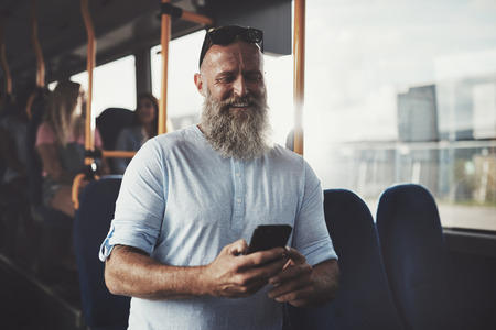 voyage: Smiling mature man with a long beard standing on a bus reading text messages on his cellphone during his morning commute