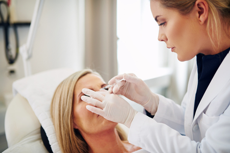 aging face: Young female doctor focused on performing a botox treatment to the forehead of a mature woman lying on a table in a beauty clinic