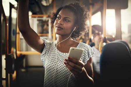 이어폰을 착용하고 스마트 폰에서 음악을 듣는 버스를 타고 웃는 젊은 아프리카 여성