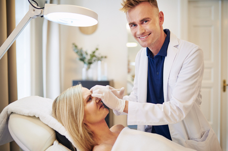 aging face: Smiling young doctor performing a botox injection to the forehead of a mature woman lying on a table in a beauty clinic