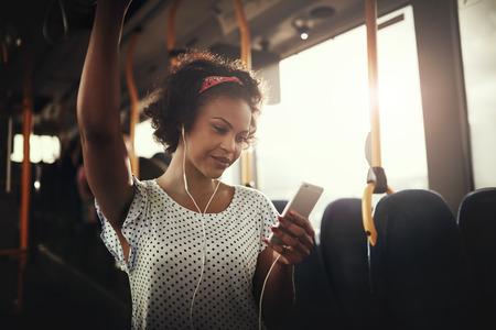スマート フォンで音楽を聞いてバスに一人で立ちながら笑みを浮かべて若いアフリカ系女性