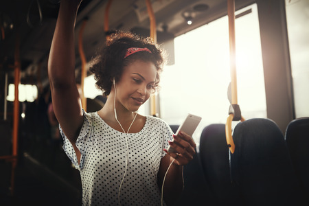 Young African woman smiling while standing by herself on a bus listening to music on a smartphone