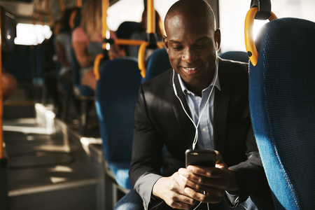 Smiling young African businessman wearing a suit sitting on a bus during his morning commute listening to music on a smartphone and earphones Archivio Fotografico
