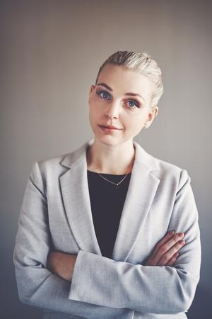 Portret van een zekere jonge onderneemster die zich alleen in een bureau met haar gekruiste wapens bevindt