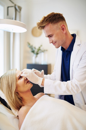 aging face: Young male doctor performing a botox injection to the forehead of a mature woman lying on a table in a beauty clinic Stock Photo