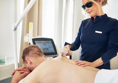 Young female beautician wearing protective glasses performing electrolysis on a man lying on a table in a beauty clinic