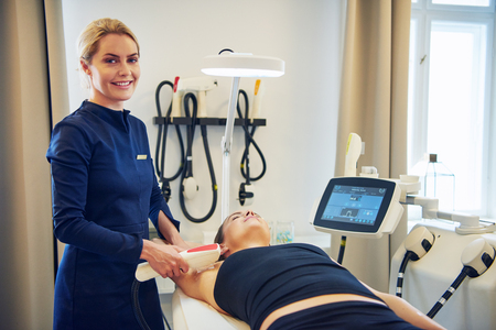 Smiling young female beautician performing an electrolysis hair removal procedure on the underarm of a woman lying on a table in a beauty clinic