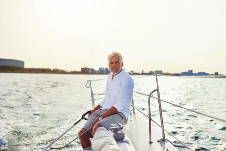 해안을 따라 항해하는 화창한 날을 즐기면서 보트의 갑판에 앉아 성숙한 남자