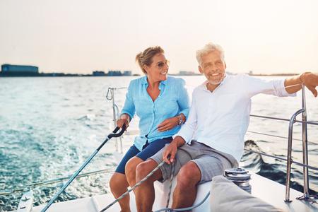 화창한 오후에 항해 동안 자신의 보트의 갑판에 함께 앉아 성숙한 커플을 웃고