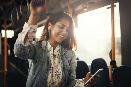 Young woman smiling while standing by herself on a bus listening to music on a smartphone