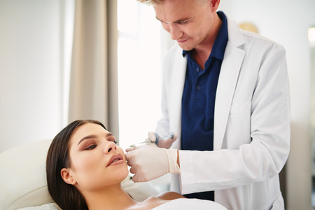 Male doctor focused on performing a injection to the cheek of a young woman lying on a table in a beauty clinic Stock Photo