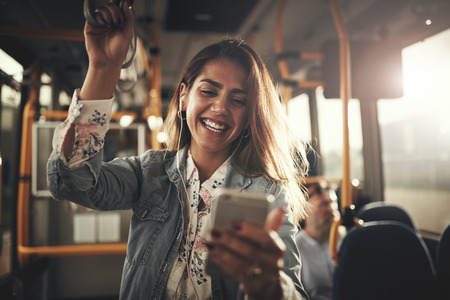 Young woman wearing earphones laughing at a text message on her cellphone while riding on a bus Banco de Imagens